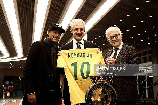 Brazilian football player Neymar da Silva Santos Junior presents a uniform to Mehmet Ali Aydinlar Chariman of the Acbadem Healthcare Group during a...