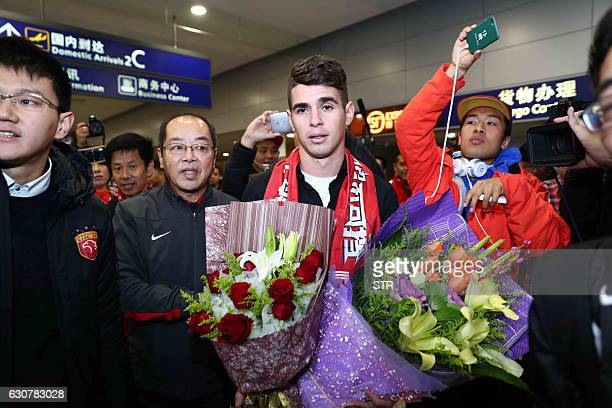 Brazilian football player Oscar is escorted as he arrives at Shanghai airport on January 2 2017 Brazilian midfielder Oscar landed in Shanghai on...