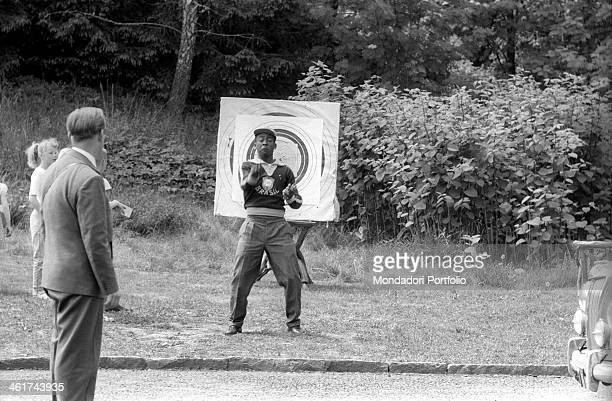 Brazilian football player Pelé joking in front of the target of a shooting galery during the 1958 World Cup Stockholm June 1958