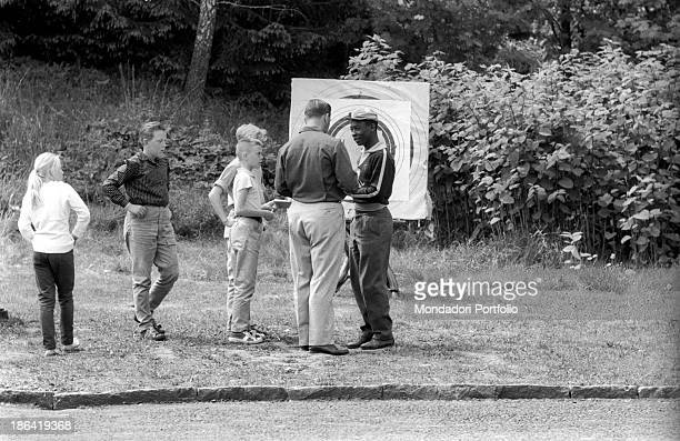 Brazilian football player Pelé talking to Swedish football player Gunnar Nordahl in front of a darts target at the 1958 FIFA World Cup Stockholm June...