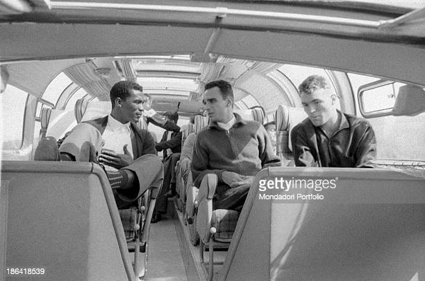Brazilian football players Didi and José Altafini relaxing with a handicapped young man who's the Brazilian team mascot in a bus at the 1958 FIFA...