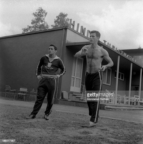 Brazilian football players Garrincha and Hilderaldo Bellini playing darts in the garden at the 1958 FIFA World Cup Stockholm June 1958