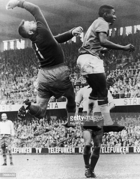 Brazilian football star Pele and Swedish goalkeeper Kalle Svensson jump for the ball during the 1958 World Cup Final in Sweden