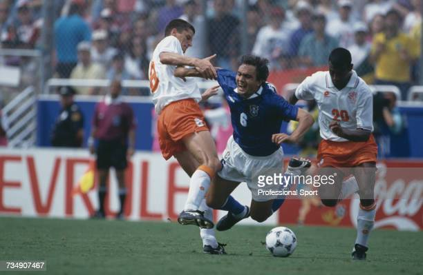 Brazilian footballer Branco falls to the ground as he is tackled by Dutch midfielder Wim Jonk with Aron Winter behind during play in the 1994 FIFA...