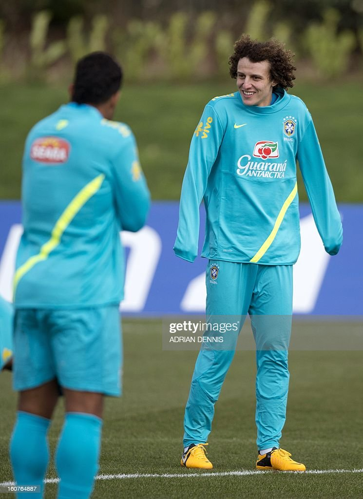 Brazilian footballer David Luiz (R) tries to keep warm during a training session at The Hive, Barnet FC's training ground in Edgware, London on February 5, 2013. Brazil are set to play England in an international friendly at London's Wembley Stadium on February 6, 2013.