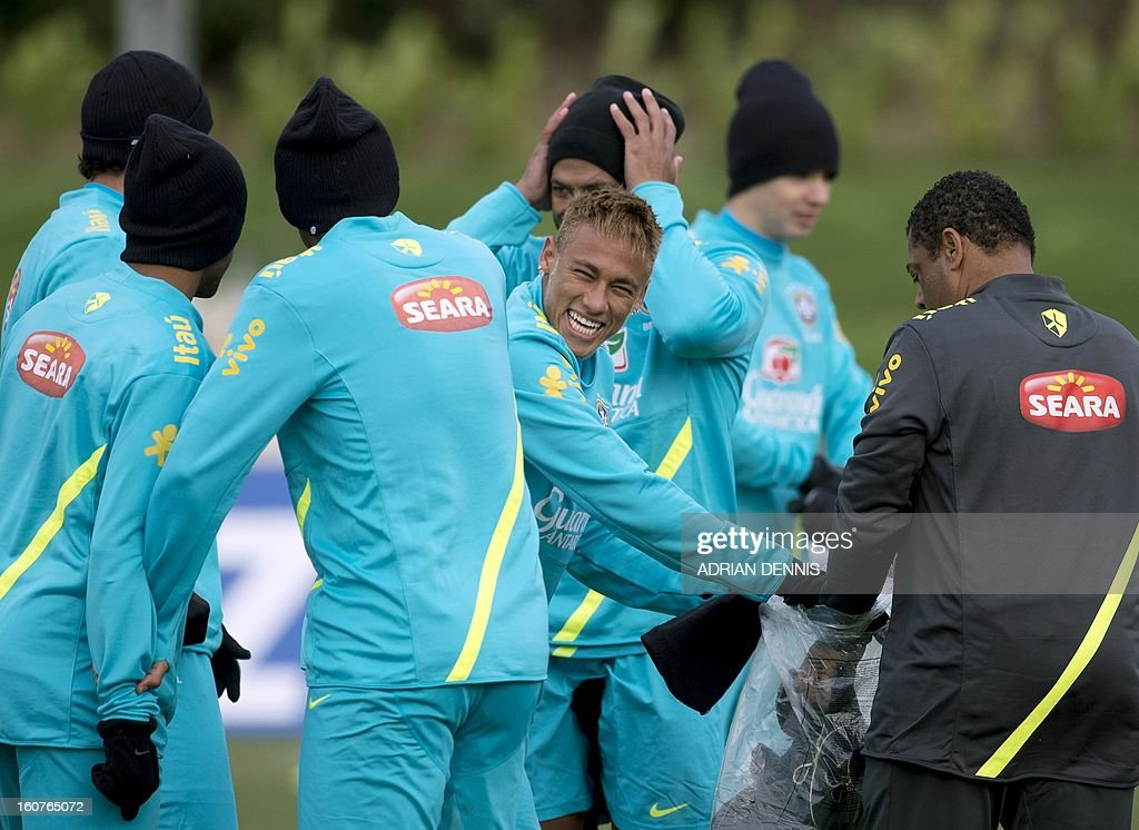 Brazilian footballer Neymar (C) grabs a pair of gloves and a hat from a coach during a training session at The Hive, Barnet FC's training ground in Edgware, London on February 5, 2013. Brazil are set to play England in an international friendly at London's Wembley Stadium on February 6, 2013. AFP PHOTO / ADRIAN DENNIS