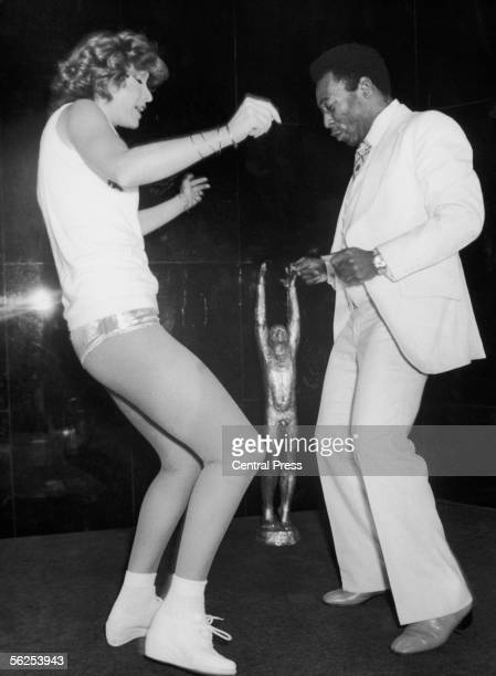 Brazilian footballer Pele dancing at Club 78 in Paris to celebrate his country's team beating France 18th May 1981 The trophy between him and his...