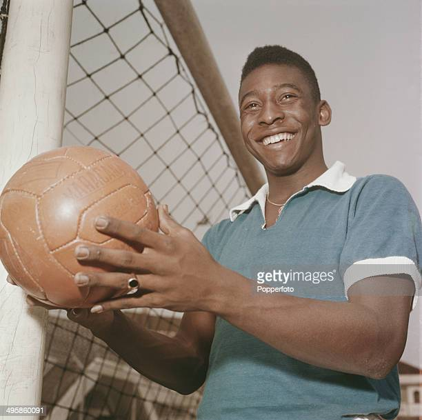 Brazilian footballer Pele posed holding a football next to a goal circa 1965