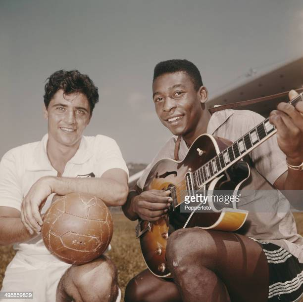 Brazilian footballer Pele posed holding a guitar beside French singer Sacha Distel holding a football circa 1965