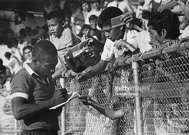 Brazilian footballer Pele signing autographs for young Mexican fans during a training session for the World Cup 1st June 1970
