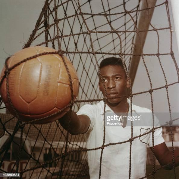 Brazilian footballer Pele wearing a Santos FC shirt retrieves a ball from the goal net circa 1960