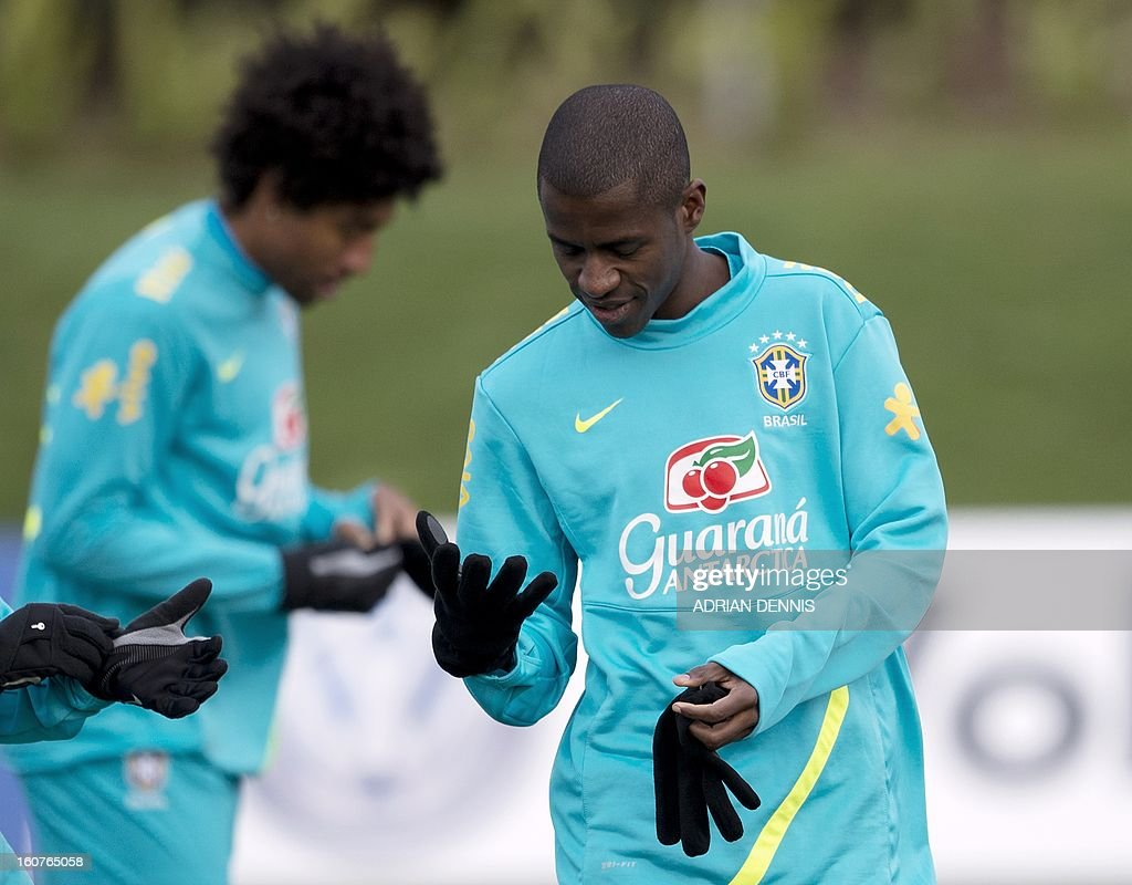 Brazilian footballer Ramires tries a pair of gloves during a training session at The Hive, Barnet FC's training ground in Edgware, London on February 5, 2013. Brazil are set to play England in an international friendly at London's Wembley Stadium on February 6, 2013.