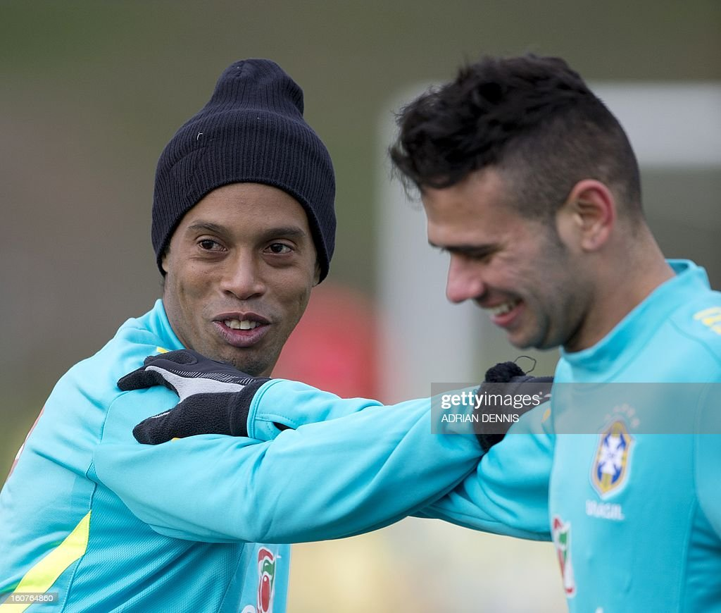 Brazilian footballer Ronaldinho (L) warms up with teammate Leandro Castan during a training session at The Hive, Barnet FC's training ground in Edgware, London on February 5, 2013. Ronaldinho admits he did not expect to be recalled by Brazil, but says he believes the squad he has returned to possesses sufficient quality to win the 2014 World Cup on home soil. After a year in the international wilderness, the 32-year-old forward is expected to feature in Brazil's friendly game against England at Wembley on February 6, 2013.