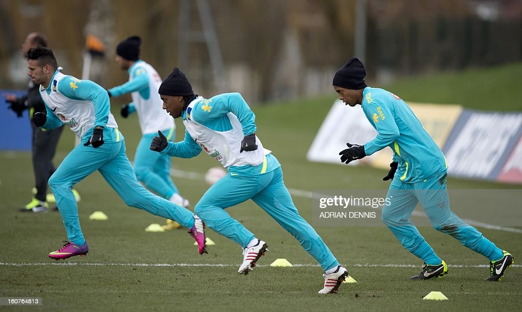 Brazilian footballer Ronaldinho (R) warms up with teammates during a training session at The Hive, Barnet FC's training ground in Edgware, London on February 5, 2013. Ronaldinho admits he did not expect to be recalled by Brazil, but says he believes the squad he has returned to possesses sufficient quality to win the 2014 World Cup on home soil. After a year in the international wilderness, the 32-year-old forward is expected to feature in Brazil's friendly game against England at Wembley on February 6, 2013.