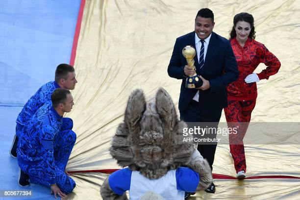 Brazilian former footaball player Ronaldo holds the trophy as the he greeted by Zabivaka the Official Mascot for the 2018 FIFA World Cup Russia prior...