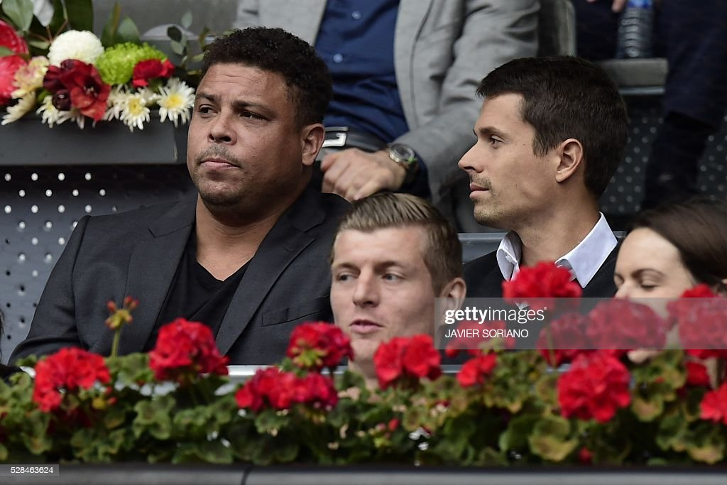 Brazilian former football player Ronaldo Nazario de Lima (L) and Real Madrid's German midfielder Toni Kroos (C bottom) attend the tennis match between Serbian tennis player Novak Djokovic vs Spanish tennis player Roberto Bautista during the Madrid Open tournament at the Caja Magica (Magic Box) sports complex in Madrid on May 5, 2016. / AFP / JAVIER