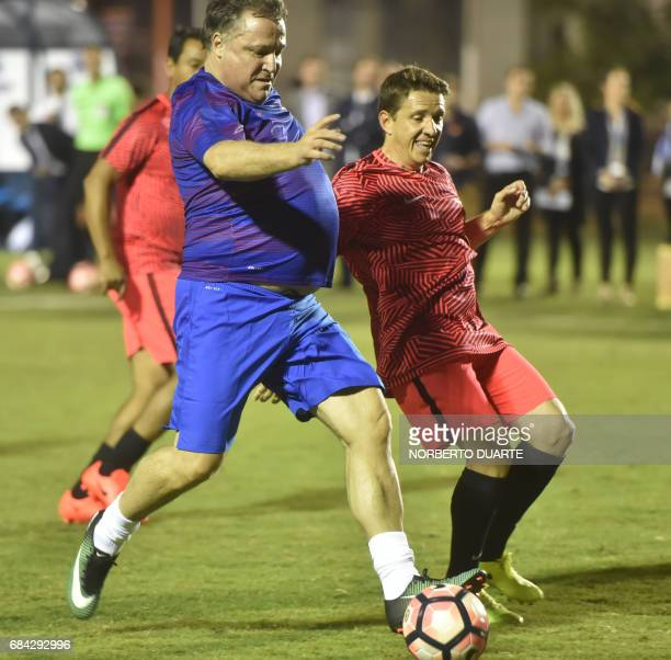 Brazilian former footballer Juninhino Paulista vies for the ball with Argentinian former footballer Daniel Bertoni during a friendly football match...