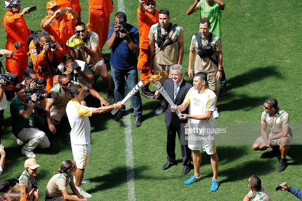Brazilian former footballer Lucio (R) and Brasilia's governor Rodrigo Rollemberg receive the Olympic flame from fireman Haudson Alves at the field of the Brasilia National Stadium in Brasilia on May 3, 2016. Embattled President Dilma Rousseff greeted the Olympic flame in Brazil on Tuesday, promising not to allow a raging political crisis, which could see her suspended within days, to spoil the Rio Games. The torch will now be carried in a relay by 12,000 people through 329 cities, ending in Rio's Maracana stadium on August 5 for the opening ceremony. / AFP / BETO