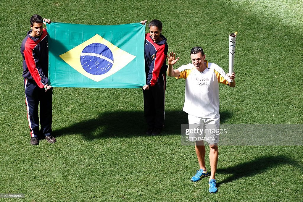 Brazilian former footballer Lucio carries the Olympic torch at the Brasilia National Stadium in Brasilia on May 3, 2016. Embattled President Dilma Rousseff greeted the Olympic flame in Brazil on Tuesday, promising not to allow a raging political crisis, which could see her suspended within days, to spoil the Rio Games. The torch will now be carried in a relay by 12,000 people through 329 cities, ending in Rio's Maracana stadium on August 5 for the opening ceremony. / AFP / BETO