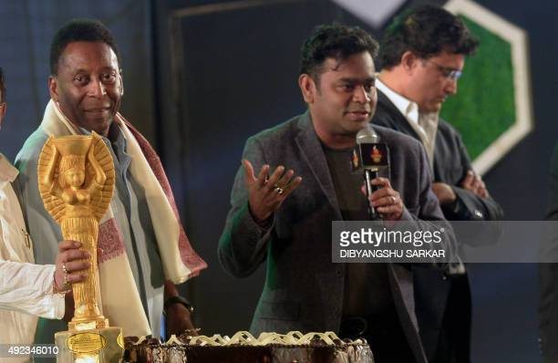 Brazilian former footballer Pele looks at a cake in the shape of the Jules Rimet trophy as Indian music composer AR Rahman sings during a visit to...