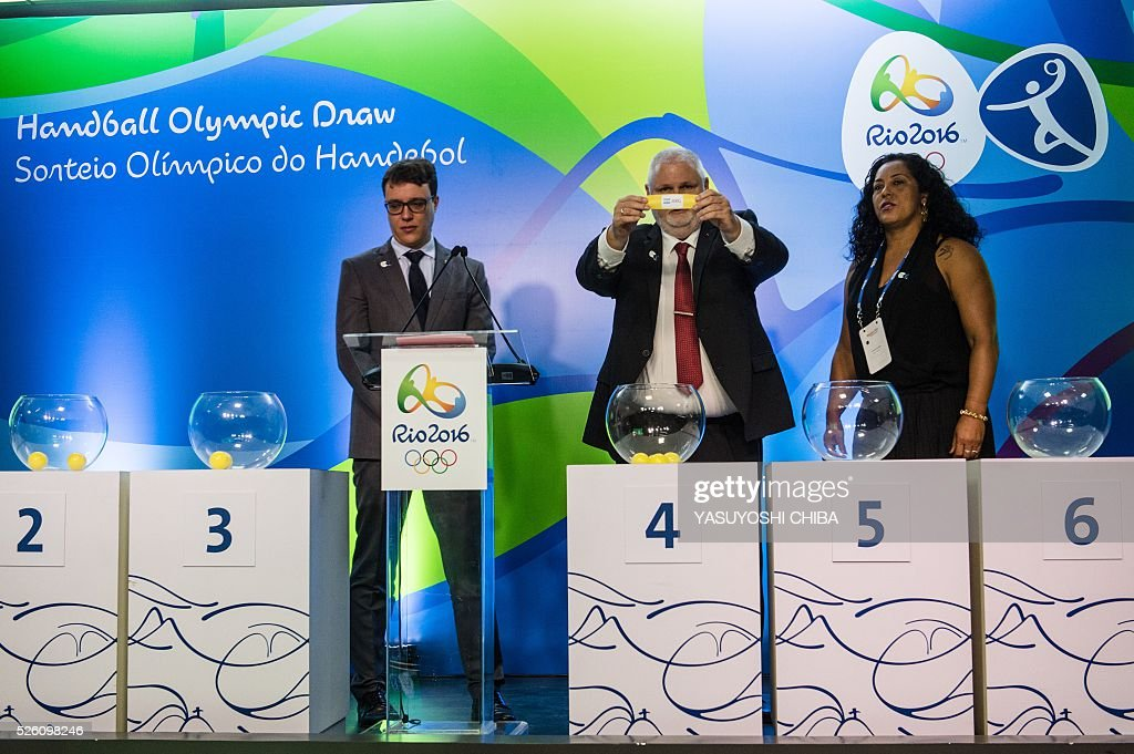 Brazilian former handball player Zeze Sales (R) and Danish Per Bertelsen (C), International Handball Federation (IHF) head of the commission of organizing and competition, during the Handball draw for Rio 2016 Olympic Games at Future Arena of Olympic Park in Rio de Janeiro, Brazil, on April 29, 2016. / AFP / YASUYOSHI