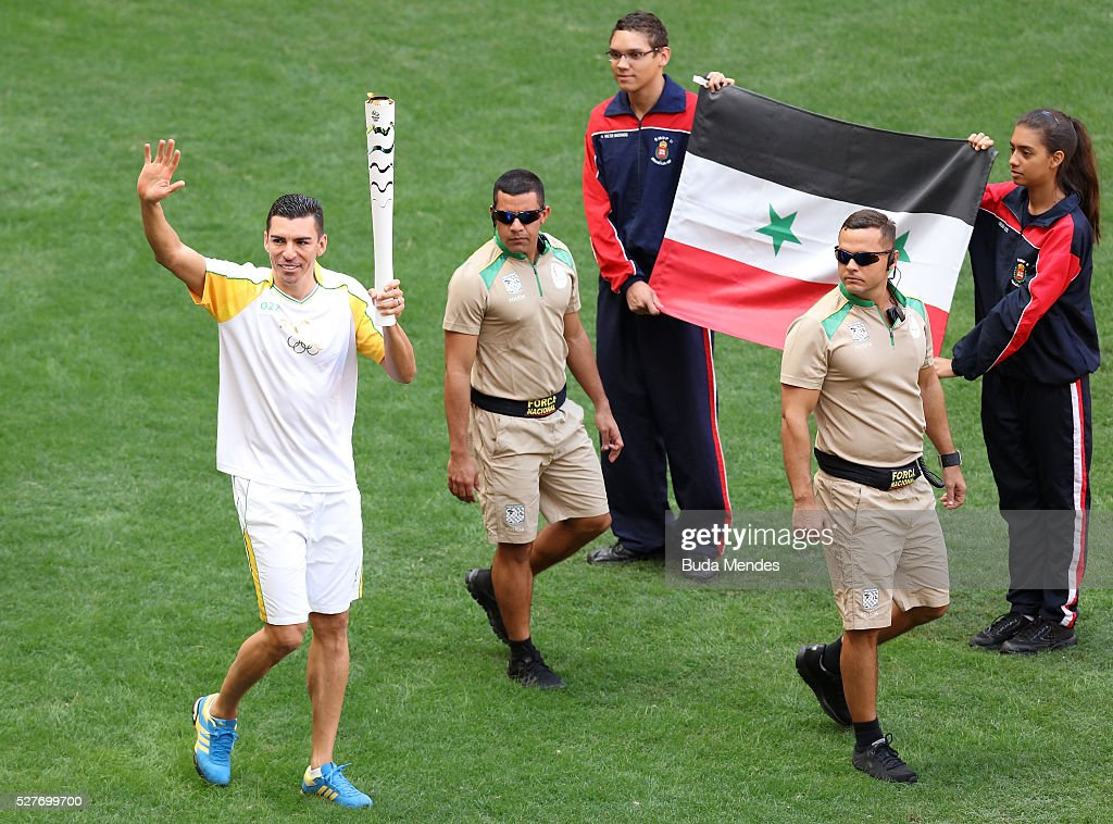 Brazilian former player Lucio holding the Olympic torch at Mane Garrincha stadium on May 3, 2016 in Brasilia, Brazil. The Olympic torch will pass through 329 cities from all states from the north to the south of Brazil, until arriving in Rio de Janeiro on August 5, to lit the cauldron.
