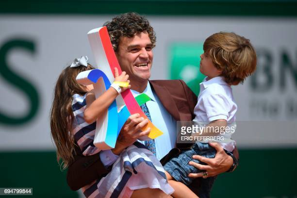 Brazilian former tennis player Gustavo Kuerten poses with his children before the men's final tennis match at the Roland Garros 2017 French Open on...