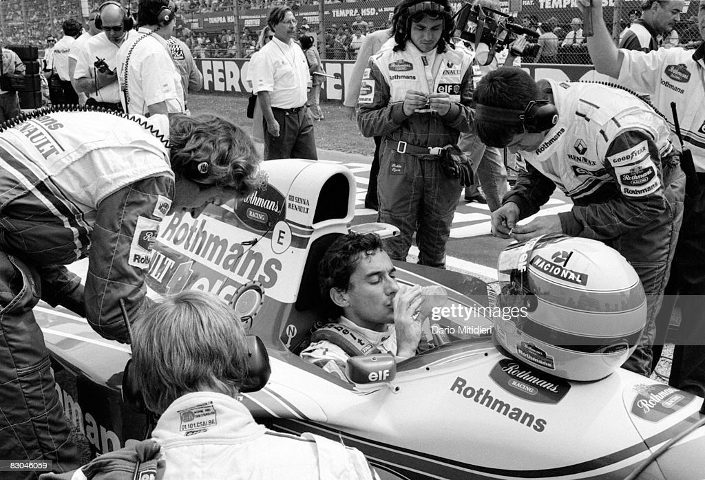 Brazilian Formula 1 race car driver Ayrton Senna (1960 - 1994) is surrounded by team mechanics as he drinks bottled water and waits on the starting line before the San Marino F1 Grand Prix on the Imola Circuit, Imola, Italy, May 1, 1994. Senna died a few hours later after an accident during the race.