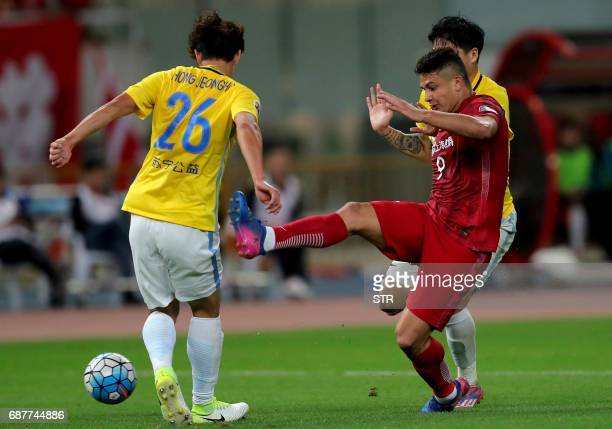 Brazilian forward Elkeson of China's Shanghai SIPG fights for the ball with Hong Jeongho of China's Jiangsu FC during their AFC Champions League...