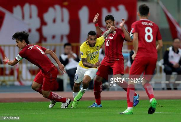 Brazilian forward Hulk of China's Shanghai SIPG fights for the ball with Alex Teixeira of China's Jiangsu FC during their AFC Champions League round...