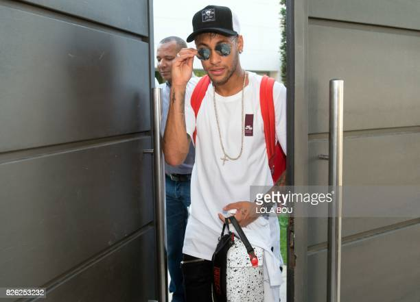 TOPSHOT Brazilian forward Neymar followed by his father Neymar da Silva Santos Sr leaves his home in Barcelona to go to the airport on August 4 2017...
