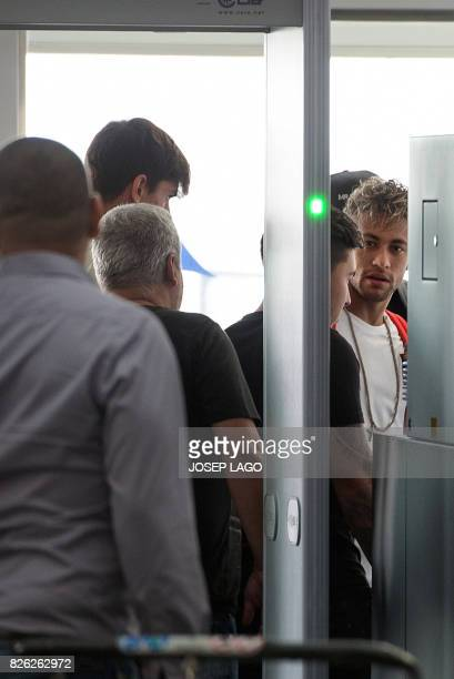 Brazilian forward Neymar goes through a security gate at the airport in Barcelona before boarding a plane to Paris on August 4 2017 Brazilian...
