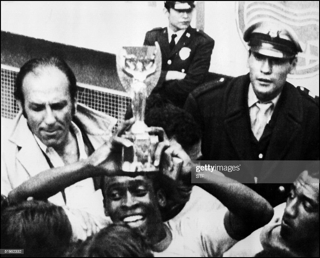 Brazilian forward PelT smiles as he holds aloft the Jules Rimet Cup after Brazil beat Italy 4-1 in the World Cup final 21 June 1970 in Mexico City. Le joueur brTsilien PelT, brandit le trophTe Jules Rimet, aprFs la victoire du BrTsil contre l'Italie, 4-1, en finale de la Coupe du monde de football, le 21 juin 1970 a Mexico.