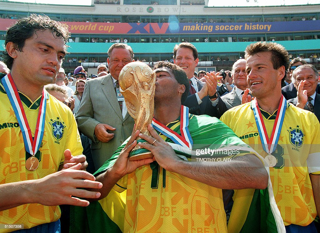 Brazilian forward Romario kisses the FIFA World Cup trophy as his teammates Branco and Dunga look on after Brazil defeated Italy 32 in the shootout...