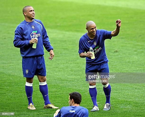 Brazilian forward Ronaldo and his teammate defender Roberto Carlos joke during a training session 18 May 2004 at the Stade de France outside Paris...