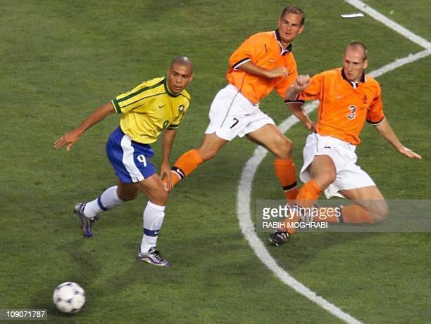 Brazilian forward Ronaldo Dutch defender Jaap Stam and midfielder Ronald De Boer tackle for the ball 07 July during the World Cup semifinal match...