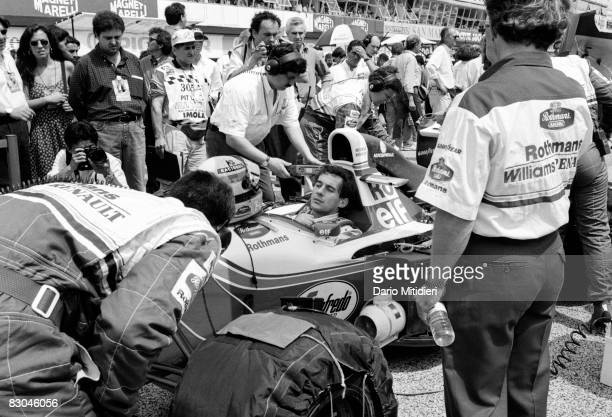 Brazilian Fromula 1 race car driver Ayrton Senna sits and waits on the starting line as his team mechanics prepare his car for the San Marino F1...