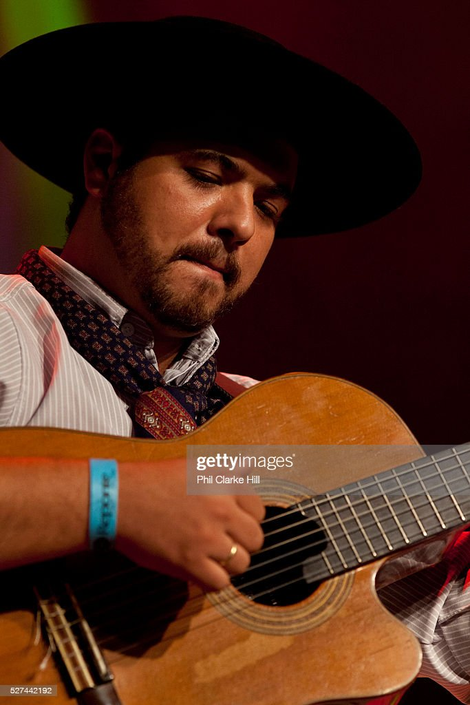Brazilian Gaucho man in traditional dress playing the guitar on stage Reponte da Cancao music festival and song competition in Sao Lorenzo do Sul RIo...