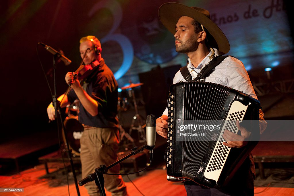 Brazilian Gaucho man in traditional dress singing and playing accordian on stage Reponte da Cancao music festival and song competition in Sao Lorenzo...