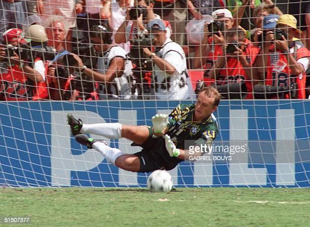 Brazilian goalkeeper Claudio Taffarel dives to stop the penalty kick of Italian defender Daniele Massaro during the shootout 17 July 1994 at the Rose...