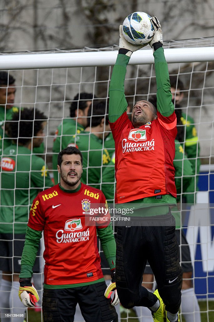 Brazilian goalkeeper Diego Cavalieri (R) catches a ball next to goalkeeper teammate Julio Cesar during a training session on March 20, 2013 in Nyon on the eve of a friendly football match between Italy and Brazil in Geneva.