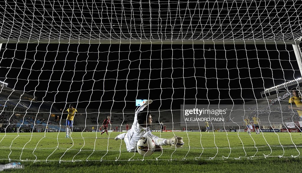 Brazilian goalkeeper Gustavo (C) fails to avoid a goal by Peruvian midfielder Edison Flores (not in picture) during their South American U-20 Championship Group B football match, at Bicentenario stadium in San Juan, Argentina, on January 18, 2013. Four teams will qualify for the Turkey 2013 FIFA U-20 World Cup.