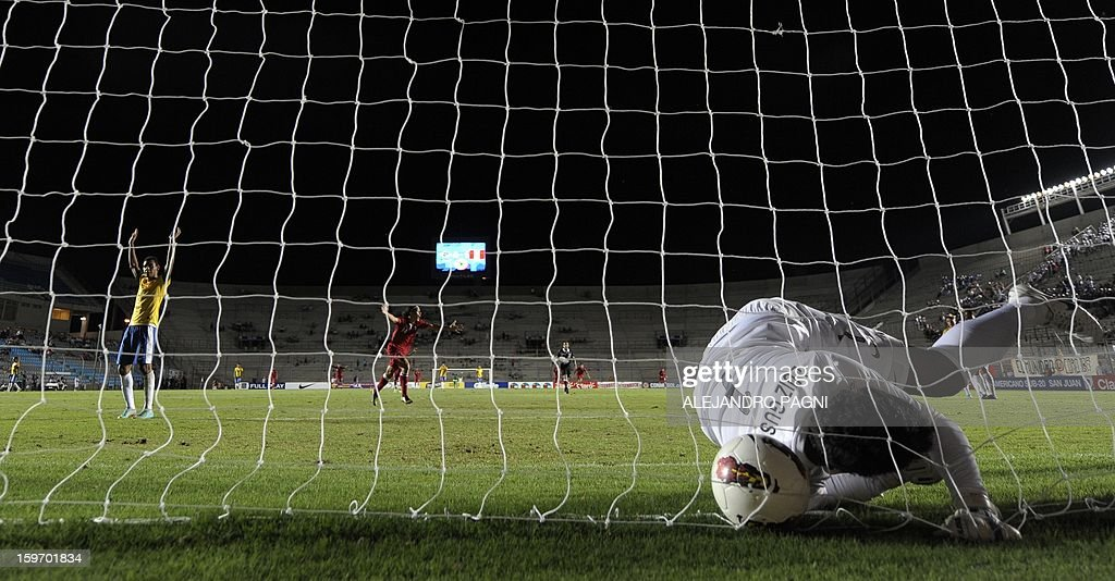 Brazilian goalkeeper Gustavo (R) fails to stop a shoot by Peruvian midfielder Edison Flores (not in picture) to score the team's second goal against Brazzil during their South American U-20 Championship Group B football match, at Bicentenario stadium in San Juan, Argentina, on January 18, 2013. Four South American teams will qualify for the FIFA U-20 World Cup Turkey 2013. AFP PHOTO / ALEJANDRO PAGNI