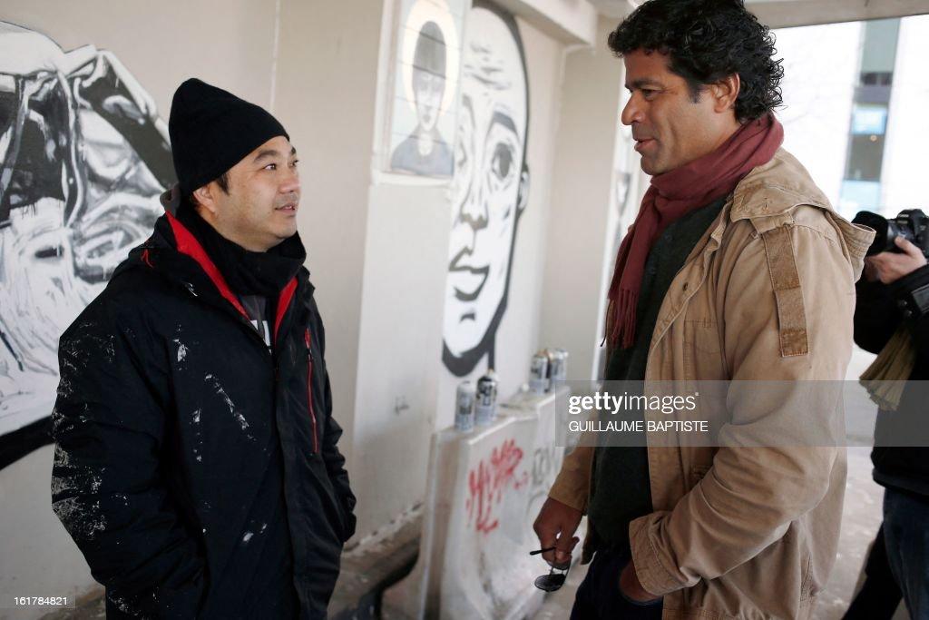 ECHEVERRIA - Brazilian Graffiti artist Walter Nomura, aka 'Tinho,' (L) speaks with Brazilian former football player Rai during a street performance on February 16, 2013 in Paris. AFP PHOTO / GUILLAUME BAPTISTE