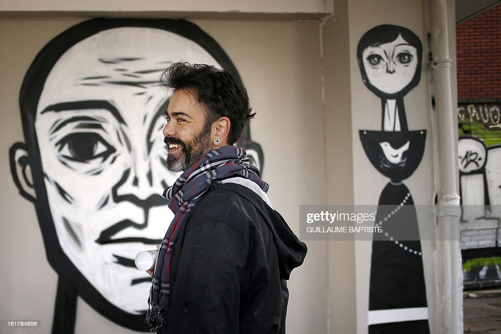 ECHEVERRIA - Brazilian Graffiti artists Speto smiles in front of his work as he takes part in a street performance on February 16, 2013 in Paris.