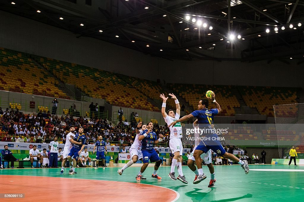 Brazilian handball teams play during a test event for Rio 2016 Olympic Games at Future Arena in the Olympic Park in Rio de Janeiro, Brazil, on April 29, 2016. / AFP / YASUYOSHI
