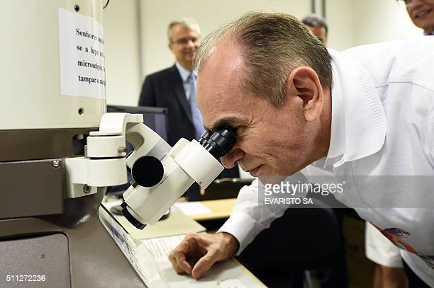 Brazilian Health Minister Marcelo Castro looks at a sample of the Zika virus through a microscope during a visit to the Biological Sciences Institute...