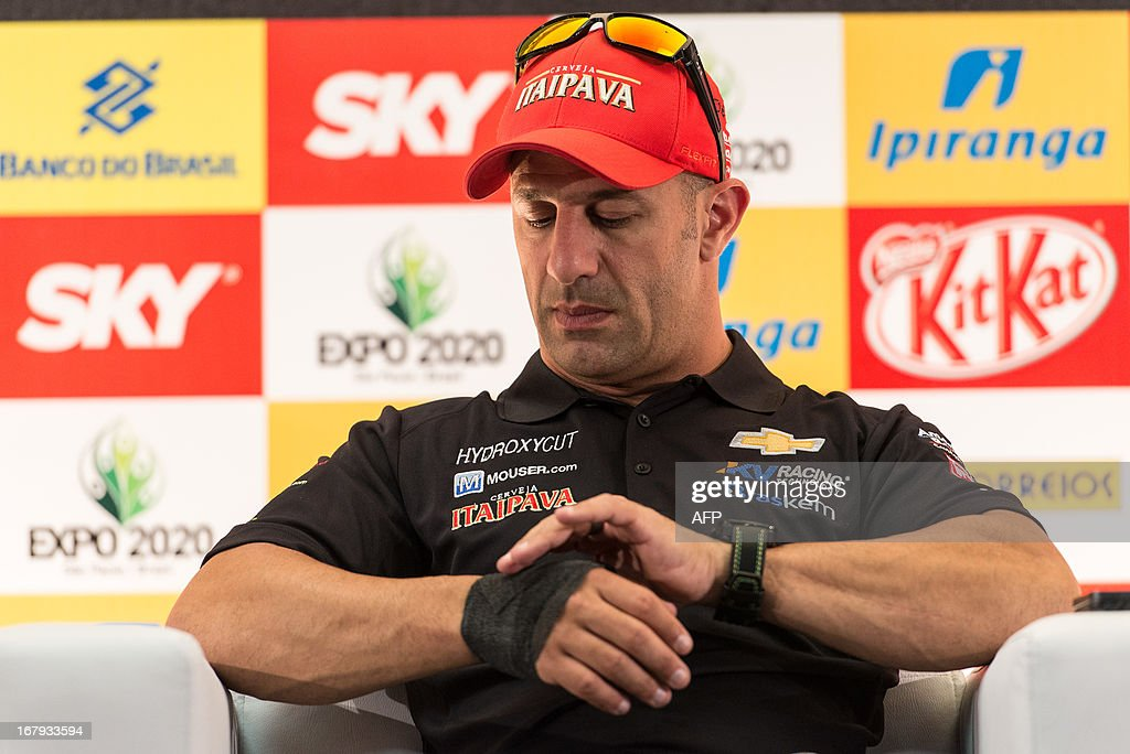 Brazilian IndyCar driver Tony Kanaan adjusts the bandage around his injured right wrist during a press conference in Sao Paulo, Brazil on May 2, 2013. The Itaipava Indy 300 Nestle race will be held on May 5. AFP PHOTO/Yasuyoshi CHIBA