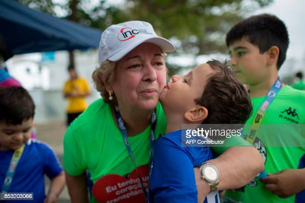 Brazilian Ivonette Balthazar who was submitted to a heart transplant one year ago hugs one of her grandchildren after participating in a...