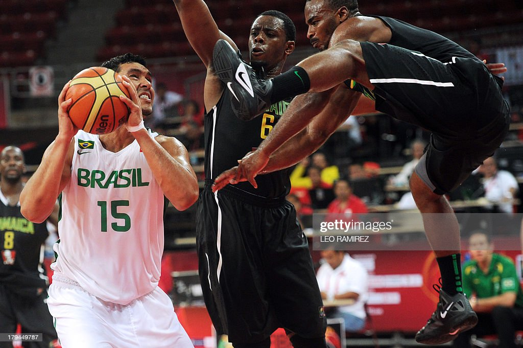 Brazilian Joao Batista (L) vies for the ball with Jamaican Patrick Ewing (C) and Akeen Scott (R) during their Spain 2014 FIBA World Cup qualifier game in Caracas on September 3, 2013. AFP PHOTO/ Leo RAMIREZ